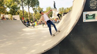 Skaters practice on the ramp at République while a protest carries on in the background. Photo by Akil Wingate.