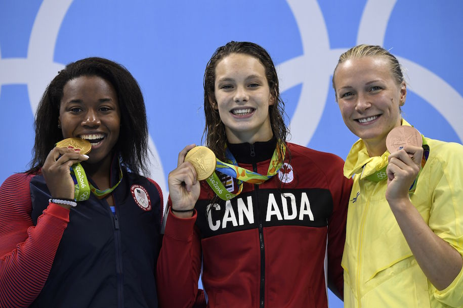 CORRECTION - Gold medallists USA's Simone Manuel (L) and Canada's Penny Oleksiak (C) pose with bronze medallist Sweden's Sarah Sjostrom on the podium of the Women's 100m Freestyle Final during the swimming event at the Rio 2016 Olympic Games at the Olympic Aquatics Stadium in Rio de Janeiro on August 11, 2016. / AFP / CHRISTOPHE SIMON / The erroneous mention appearing in the metadata of this photo by CHRISTOPHE SIMON has been modified in AFP systems in the following manner: BRONZE instead of SILVER. Please immediately remove the erroneous mention[s] from all your online services and delete it from your servers. If you have been authorized by AFP to distribute it to third parties, please ensure that the same actions are carried out by them. Failure to promptly comply with these instructions will entail liability on your part for any continued or post notification usage. Therefore we thank you very much for all your attention and prompt action. We are sorry for the inconvenience this notification may cause and remain at your disposal for any further information you may require. (Photo credit should read CHRISTOPHE SIMON/AFP/Getty Images)