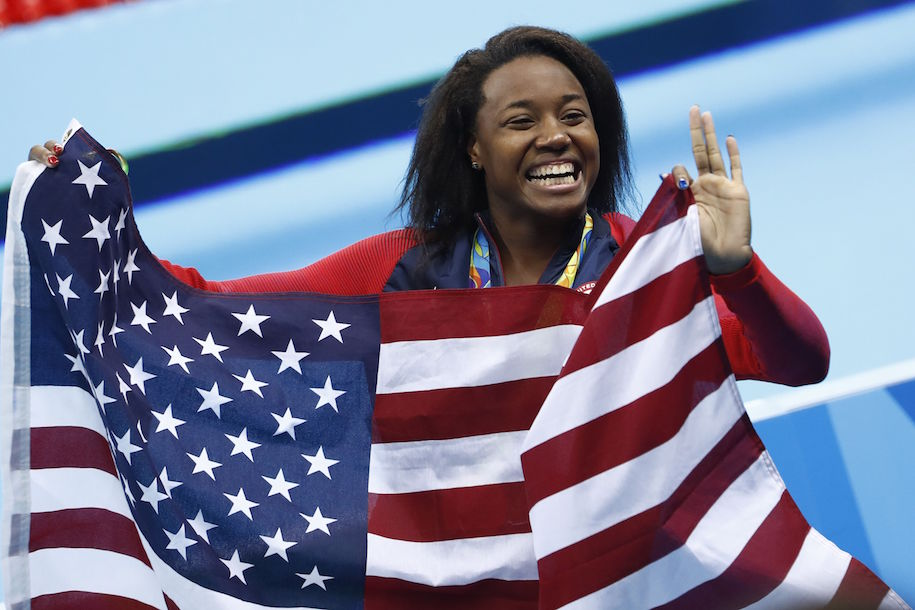 Gold medallist USA's Simone Manuel wave her national flag during the medal ceremony of the Women's 100m Freestyle Final during the swimming event at the Rio 2016 Olympic Games at the Olympic Aquatics Stadium in Rio de Janeiro on August 11, 2016. / AFP / Odd Andersen (Photo credit should read ODD ANDERSEN/AFP/Getty Images)
