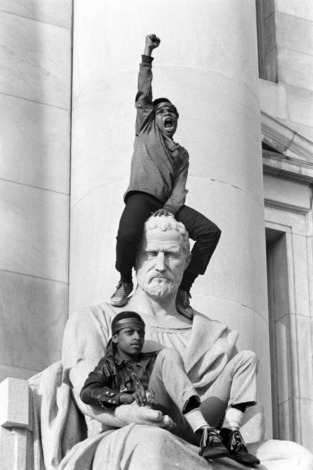 May 1, 1970 – New Haven, Connecticut, USA: Boy gives raised fist salute as he and a friend sit on a statue in front of the New Haven County Courthouse during a demonstration of 15,000 people during the Bobby Seale / Ericka Huggins trial. Bobby Seale, Chairman of the Black Panther Party is on trial along with Ericka Huggins for murder. Both are acquitted.(Stephen Shames/Polaris)